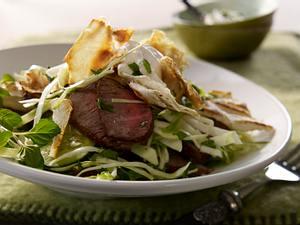 Geröstete Fladenbrotstücke mit Krautsalat, Salatgurke und Lammfleisch Rezept