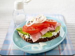Tomatenbrot mit Ricotta, Kochschinken und Zwiebelringen auf Salatblatt Rezept