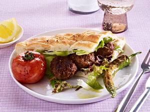 Adana Kebab auf Fladenbrot und Salat Rezept