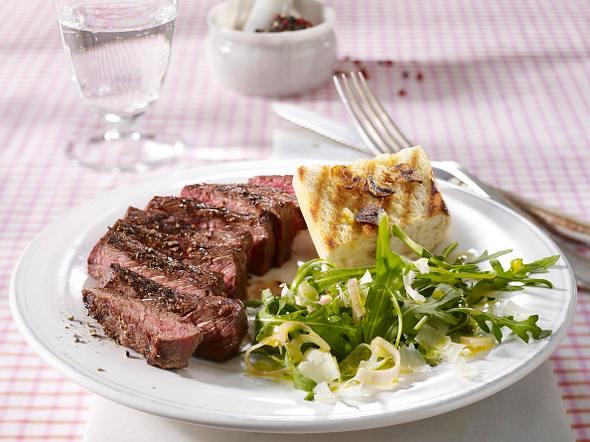 Gegrilltes Rumpsteak auf Rucola-Salat mit feinen Parmesanspänen und Knoblauch-Baguette Rezept
