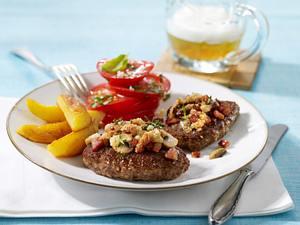 Hacksteak mit Speck-Pilzkruste, Kartoffelspalten und Tomatensalat. Rezept