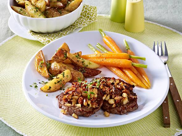 Rinderschnitzel mit Nusskruste, Kartoffelecken und glasierten Möhren Rezept