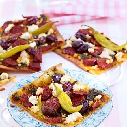 Sommerlicher Flammkuchen mit Ziegenfrischkäse, Chorizo, Peperoni, Oliven und Pesto Rezept
