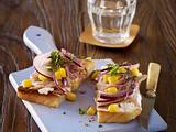 Toast mit Ziegenfrischkäse, Thunfisch, roten Zwiebelringen und Mais Rezept